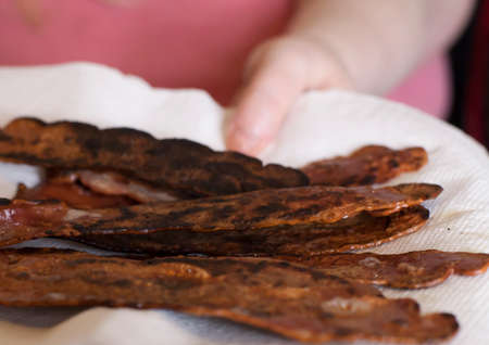 Greasy cooked bacon draining on a paper towel