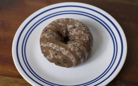 Close up of a single blueberry donut on a serving plate