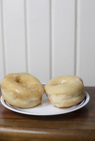 Two sweet, glazed donuts on a serving plate Stock Photo