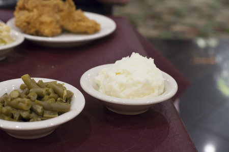 Portions of food on a table with the focus on the green beans and mashed potatoes Stock Photo