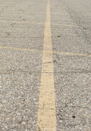 Yellow lines marking off parking spaces in an asphalt lot