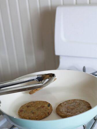 彼らはストーブの上にフライと野菜のハンバーガーを反転