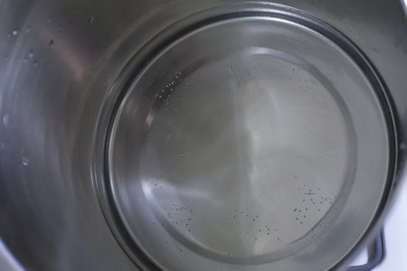 Close up of water in a pot before it starts to boil