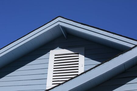 Close up of awning and attic window of a blue and white house Imagens