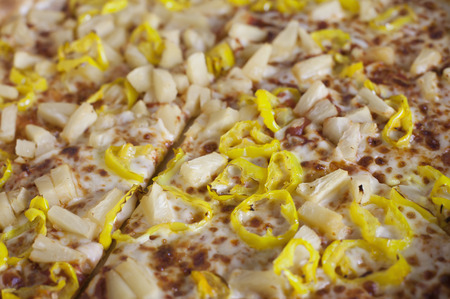 Close up of a pizza with banana pepper and pineapple toppings