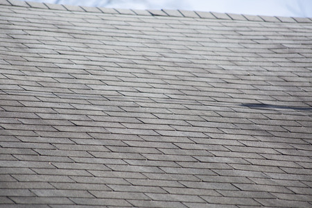 Damaged shingles on a roof after a storm Stock Photo