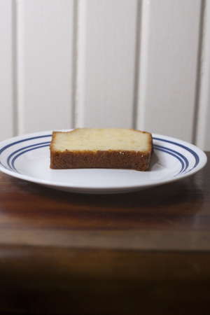 A single slice of pound cake on a small plate