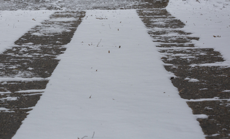Driveway with snow in the yard between the tire tracks 免版税图像