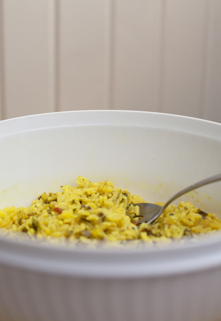 Caribbean rice in a white serving container with a silver serving spoon