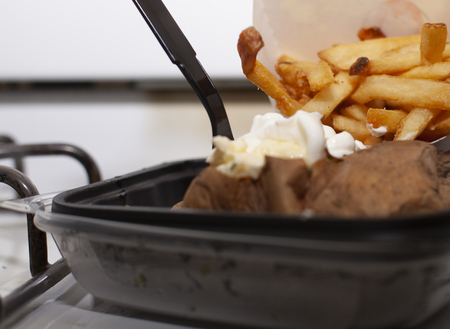 French fries and baked potato loaded with butter and sour cream Stok Fotoğraf