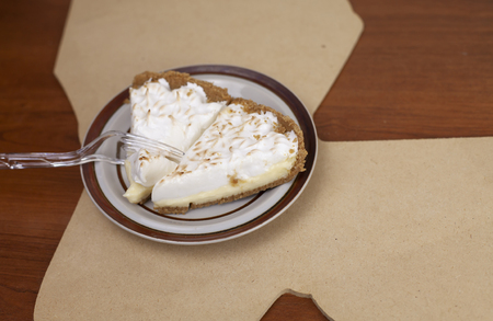 Two slices of lemon meringue pie plated on a cutout of the state of Louisiana Stok Fotoğraf