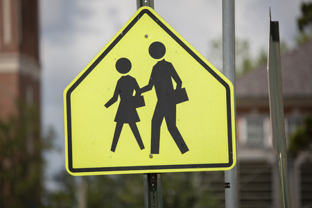 Yellow traffic sign indicating a school zone and crosswalk