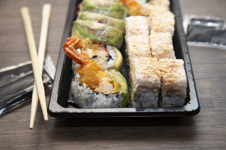 Close up of sushi rolls with crab, avocado, and shrimp, with chopsticks and soy sauce to the side
