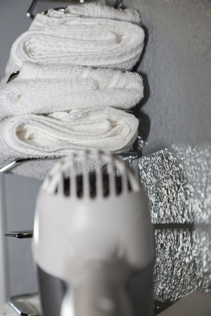 Blow dryer and neatly stacked white towels in a bathroom