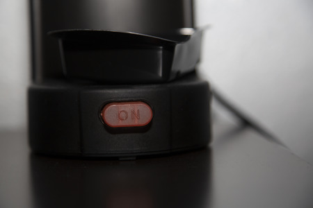 Close up of the on button of a coffee maker