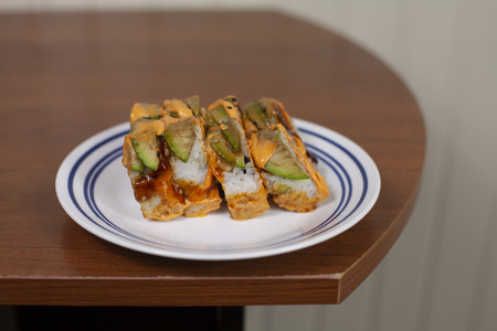 Sushi roll filled with cream cheese and crab and topped with avocado Stok Fotoğraf