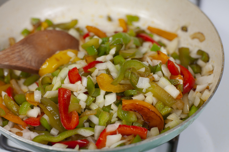 Stir frying green, orange, red, and yellow bell peppers and white onion in skillet Stok Fotoğraf