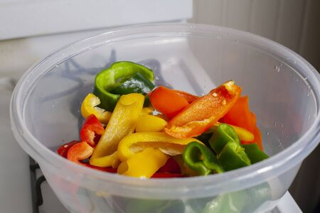 Bowl of sliced green, orange, red, and yellow bell peppers and poblano peppers