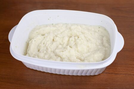 Large dish of creamy mashed potatoes prepared with chives