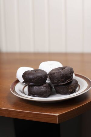 Powdered and chocolate donuts stacked on a serving plate Stock Photo