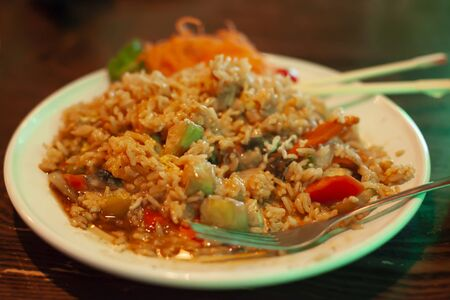 A large portion of stir fried rice and veggies on a white plate Stock Photo
