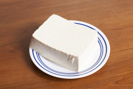 Block of raw tofu on a small serving plate