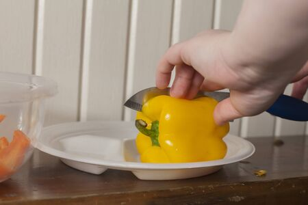 Woman cutting a yellow bell pepper on a polystyrene plate