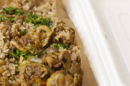 Spicy eggplant, mushrooms, rice and cilantro dish in a carryout box