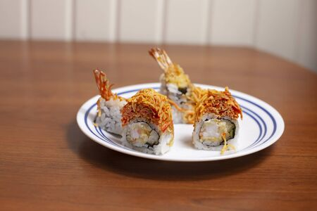 Slices of crunchy dragon roll sushi with shrimp tempura on a serving plate Stock Photo