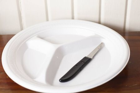 Empty white polystyrene plate with a single paring knife