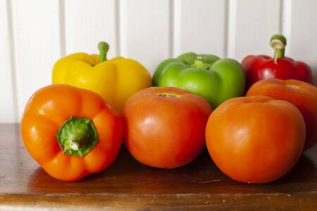 Yellow, green, red, and orange bell peppers with three ripe, red tomatoes