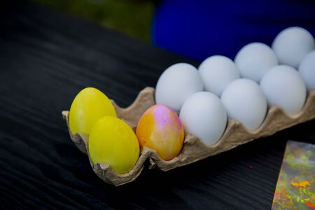 Close up of a dozen plastic Easter eggs in a carton with two eggs dyed yellow and one dyed pink and yellow