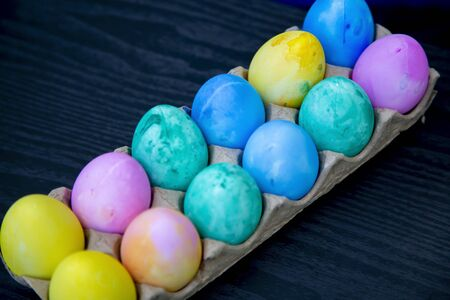 A dozen plastic Easter eggs dyed yellow, pink, green, blue and purple Stock Photo