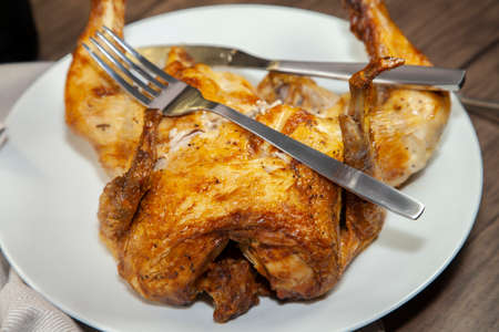 Fork and knife on a cut, roasted chicken Standard-Bild