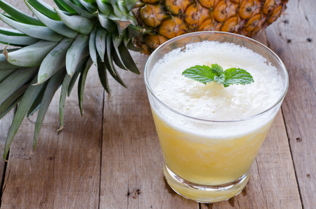 pineapple  glass: Glass of pineapple smoothie with fresh mint leaves and pineapple on wooden table