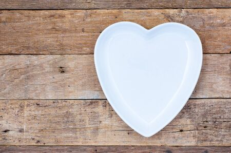 white space: Empty heart-shaped plate on wooden board top view from above