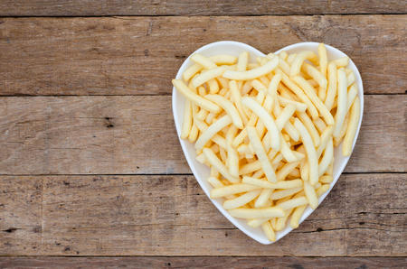 flavour: Potato french fries flavour snack in heart-shaped plate prepared on wooden table top view from above Stock Photo