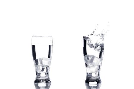 vasos de agua: Dos vasos de agua con cubitos de hielo cuál salpicaduras. Foto de archivo