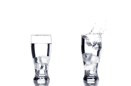 which one: Two glasses of water with ice cubes which one splashing. Stock Photo