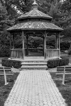 Front of gazebo with wood and steel benches in front. Outdoor gazebo with shrubs and grass. Shady retreat in backyard. Outdoor rotunda summerhouse. Outside platform.