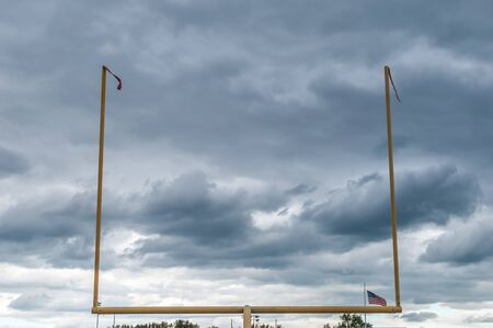 Outdoor football field goal with gloomy rainy sky background.