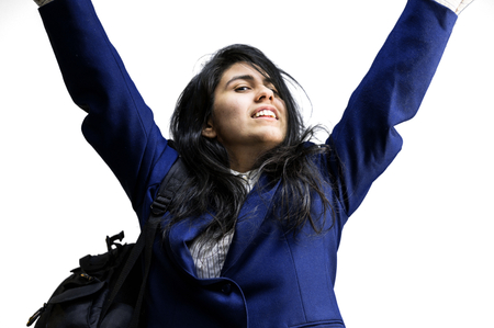latina teen: Happy latina teen girl wearing a backpack with arms raised in the air Stock Photo
