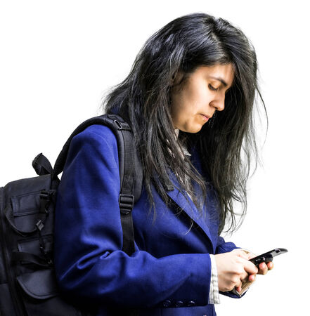 latina teen: Side shot of latina teen girl with a backpck on looking down at cell phone Stock Photo