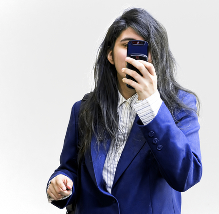 teen girl: Latina teen girl holding cellphone pointed at camera