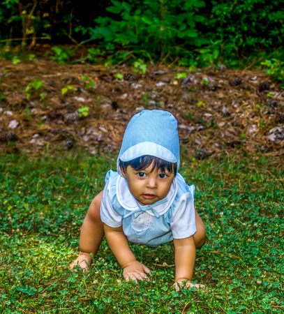 Latino baby dressed up and crawling outside in the grass