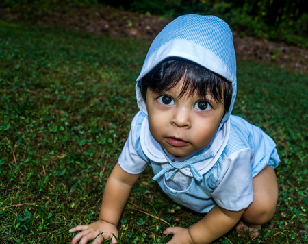 Close up shot of latino baby dressed up and crawling outside in the grass