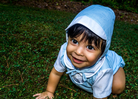 Close up shot of smiling latino baby dressed up and crawling outside in the grass