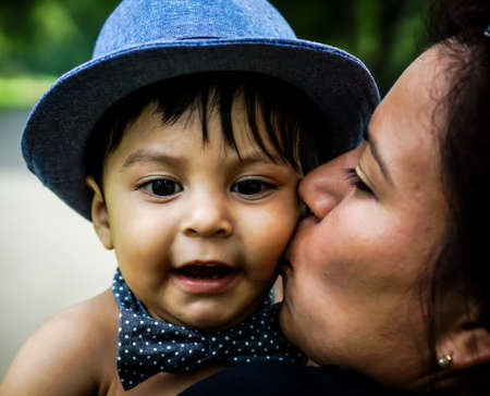 nephew: Smiling latino baby wearing a blue hat and bow tie being kissed on cheek by female adult family member Stock Photo