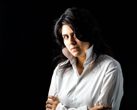 latina teen: Latina teen in white long sleeved shirt standing in front of black backdrop with arms crossed and looking at the camera Stock Photo