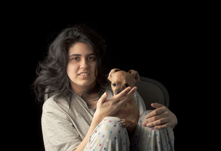latina teen: Low key shot of latina teenage girl holding her chihuahua dog and looking at the camera with a smile on her face; the dogs ears are curled back to create a funny appearance.